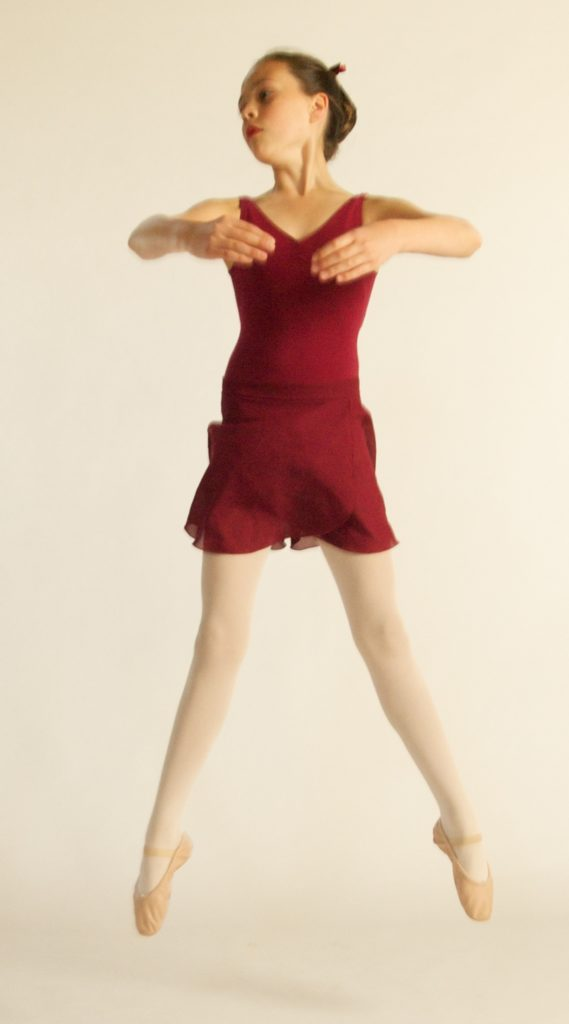 Young dancer jumps into the air with stretched legs and feet, turning her head to the right